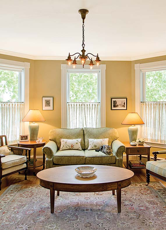 Furnished with period lighting fixtures, antique rugs, and furniture collected by the homeowner, the interior of the 1894 house suits her contemporary life.