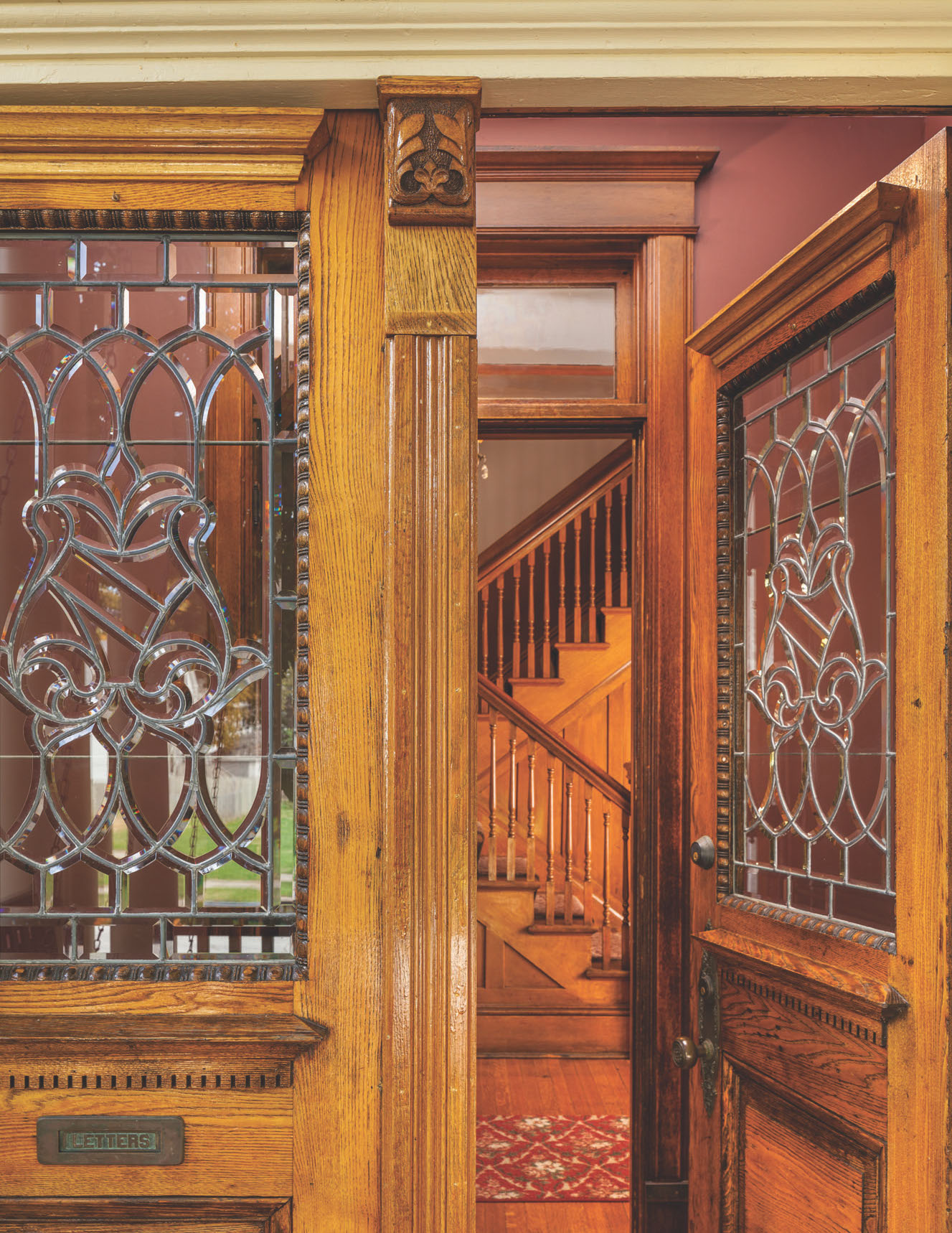 Handsome oak entry doors are period replacements for missing originals; the beveled-glass panels are also salvage and complement those still on the house. Staircase and trim are original.