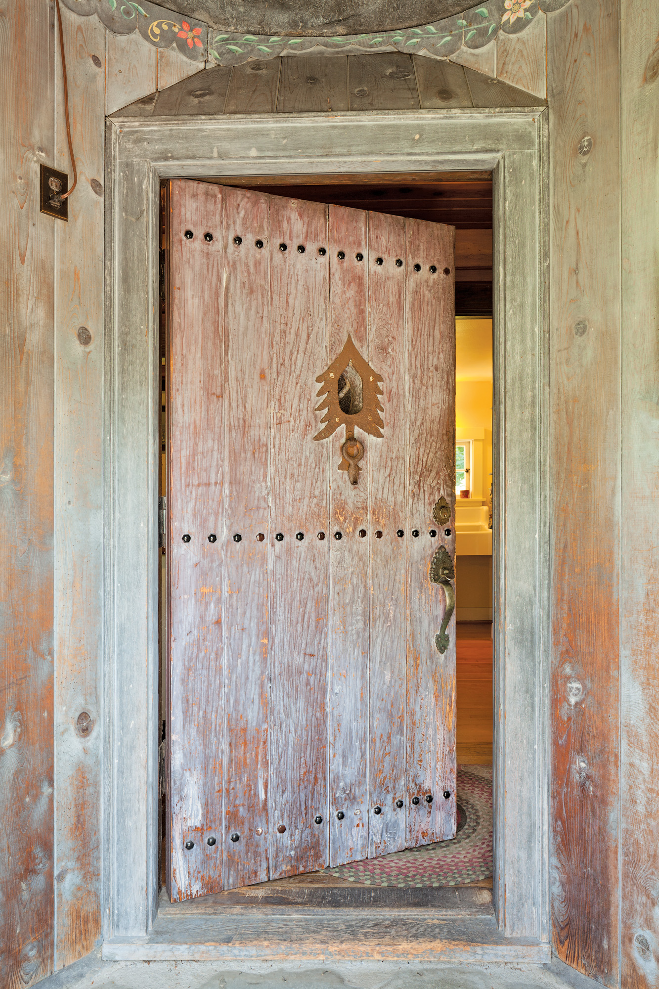 The carved cedar front door has decorative bolts and a fir tree peep-hole and knocker.