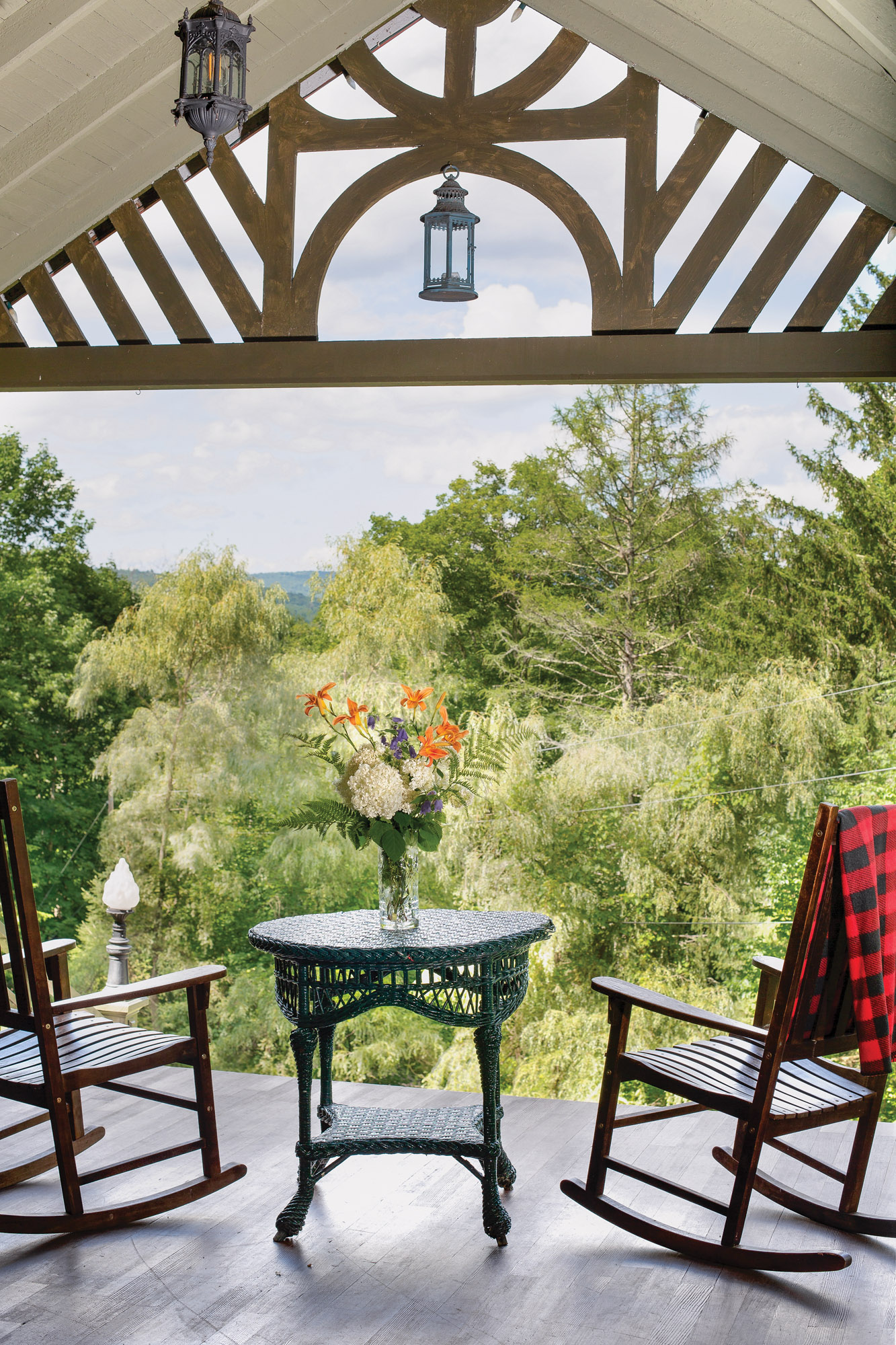 The porch at Spillian is furnished with rocking chairs and a handful of cherished wicker tables dating from the house's history as a hotel.
