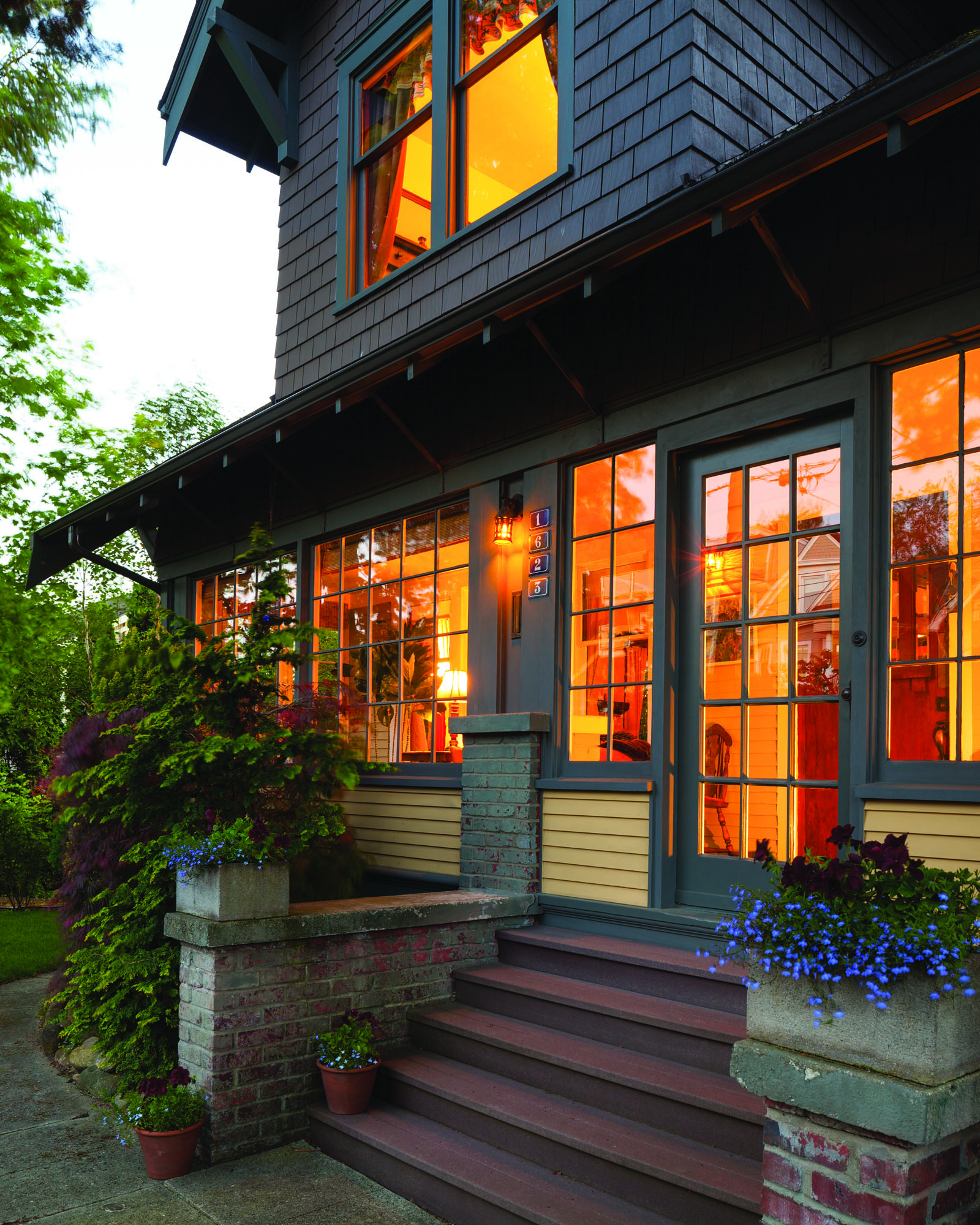 Liberated from asphalt siding, the original shiplap was restored and painted. Paint colors are Benjamin Moore 'Chestertown Buff' and 'Kendall Charcoal'. The enclosed sun-porch glows at dusk. opposite (inset) Homeown