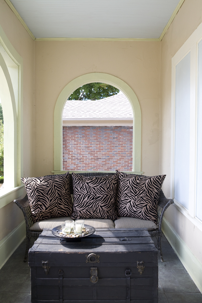 Faith's grandmother's wicker loveseat graces the upstairs sleeping porch, restored to its original use.