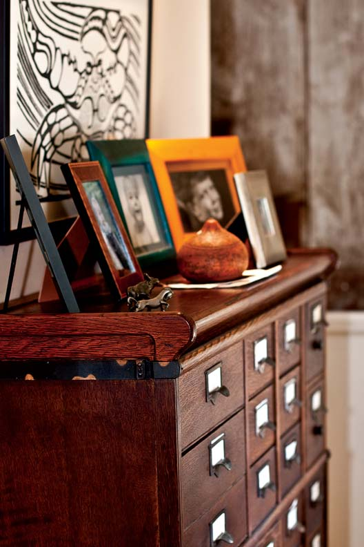 Family photos taken by Neil, an avid amateur photographer, are arranged lovingly on antique furniture throughout the home.