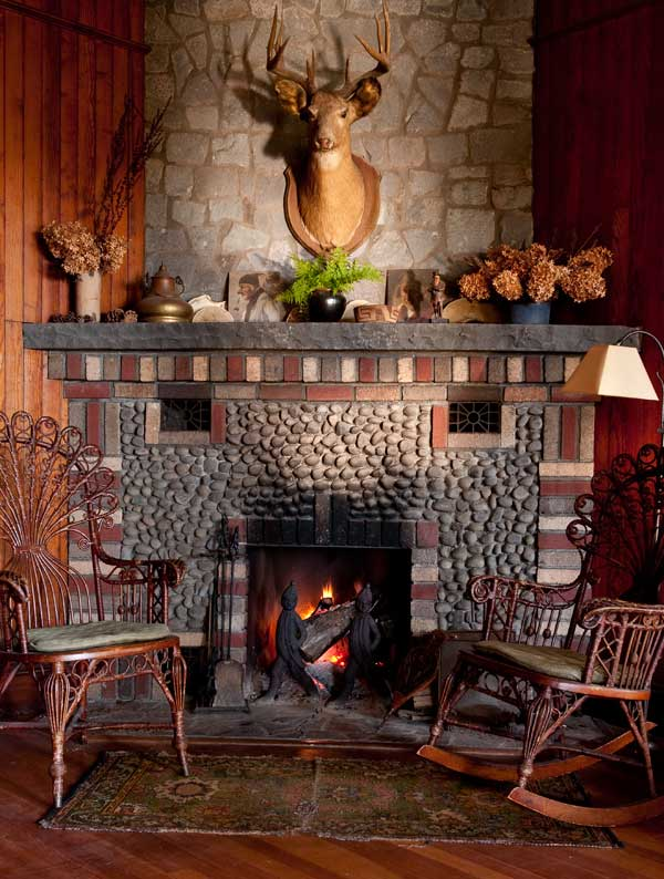 Fancy wicker chairs original to the house rest in front of the pebble and brick fireplace. Note the antique Hessian-soldier firedogs, so appropriate for this house built by German immigrants.