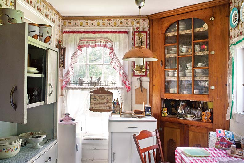 Much evolved, a true farmhouse kitchen retains metal cabinets along with the old corner cupboard, long-ago wallpaper, and an electrified kerosene lantern on a pulley.