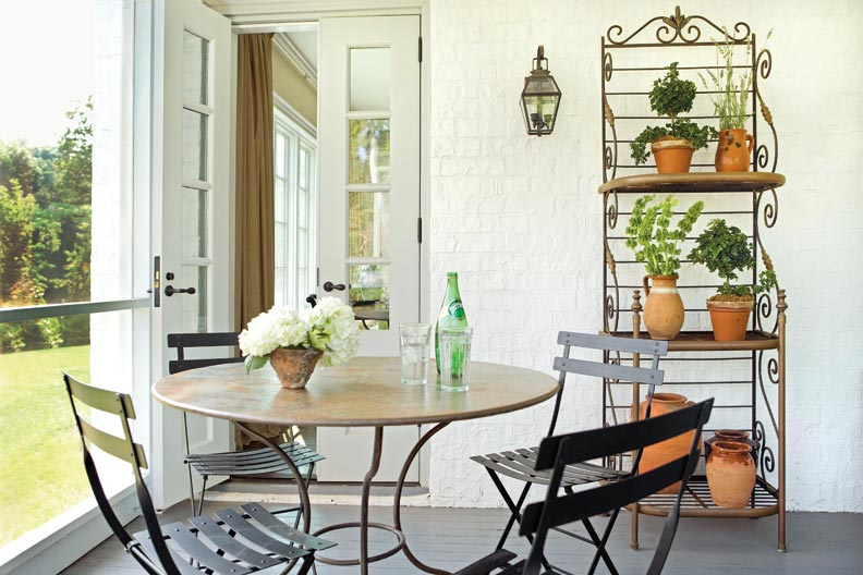An enclosed porch with tongue-and-groove decking and a painted brick wall provides a light, airy space for houseplants or just enjoying the scenery.