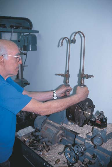 Chris Christou holds a pair of 1880s Fuller-ball faucets—now with rebuilt internal working parts.