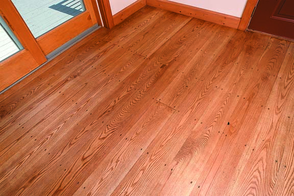 Picking a floor finish means weighing aesthetics against the realities of maintenance. The authors' linseed-oil finish on their ash floor is museum accurate, but it may need touch-ups in a modern household.
