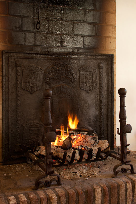 Adding a fireback to your hearth is a do—it helps increase the efficiency of the fireplace.