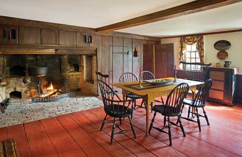 The huge 17th-century fireplace was uncovered during restoration. The owners use this, the original hall, as a dining room. The summer beam and dentil molding over the fireplace were reproduced.
