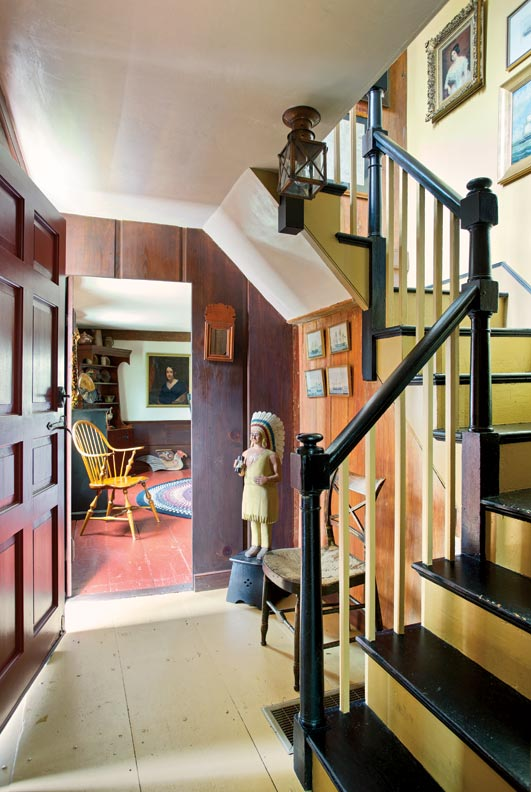 The steep, narrow stairs in the front hall date to about 1830. About the cigar-store Indian, owner Kathy Bruce says the house has made them antiques collectors.