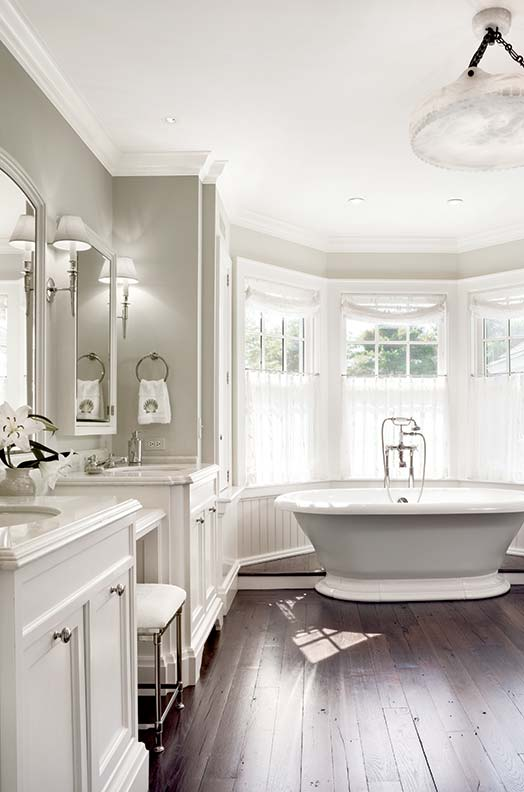 Hardwood floors and a soaking tub create a country feel in this seaside bath by John B. Murray.