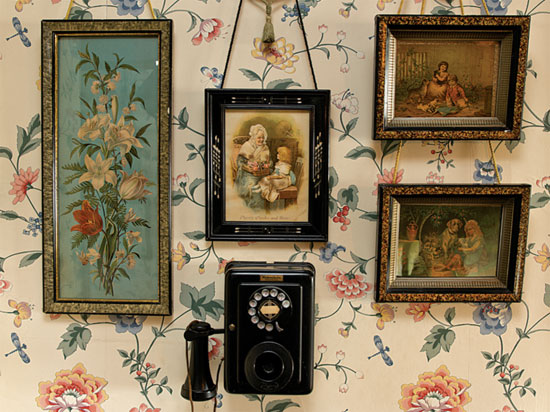 Framed Victorian prints and a ca. 1920 wall phone are in the upstairs hall.