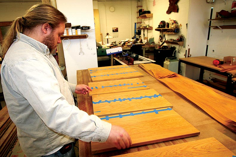 Master carpenter Stafford Norris carefully matches up wood veneer.