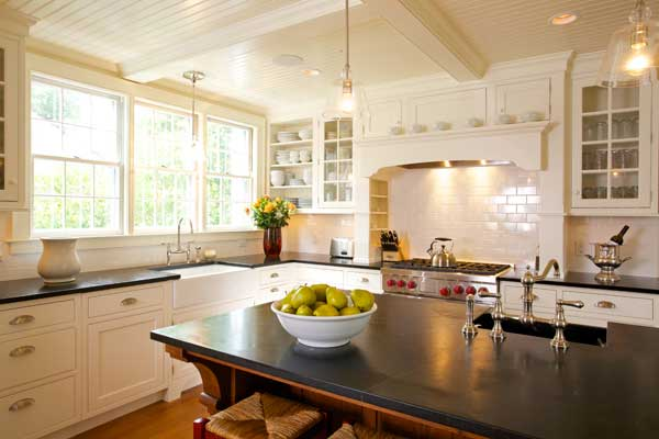 """Frankly modern in function, the new kitchen has a traditional look: a stove """"hearth,"""" beautiful millwork, and a furniture-like island."""