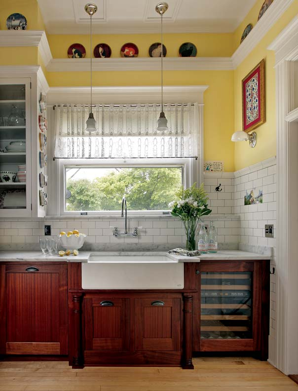 Dark-stained lower cabinets help ground the room and add to the French bakery feel. A farmhouse sink and gooseneck faucet are a period-perfect combination.
