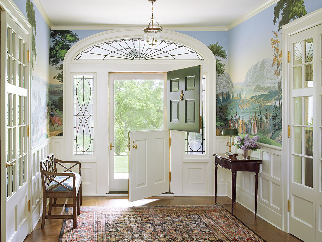 The client is in the shipping business so he selected nautically themed Zuber wallpaper depicting trading seaports for the entry hall.