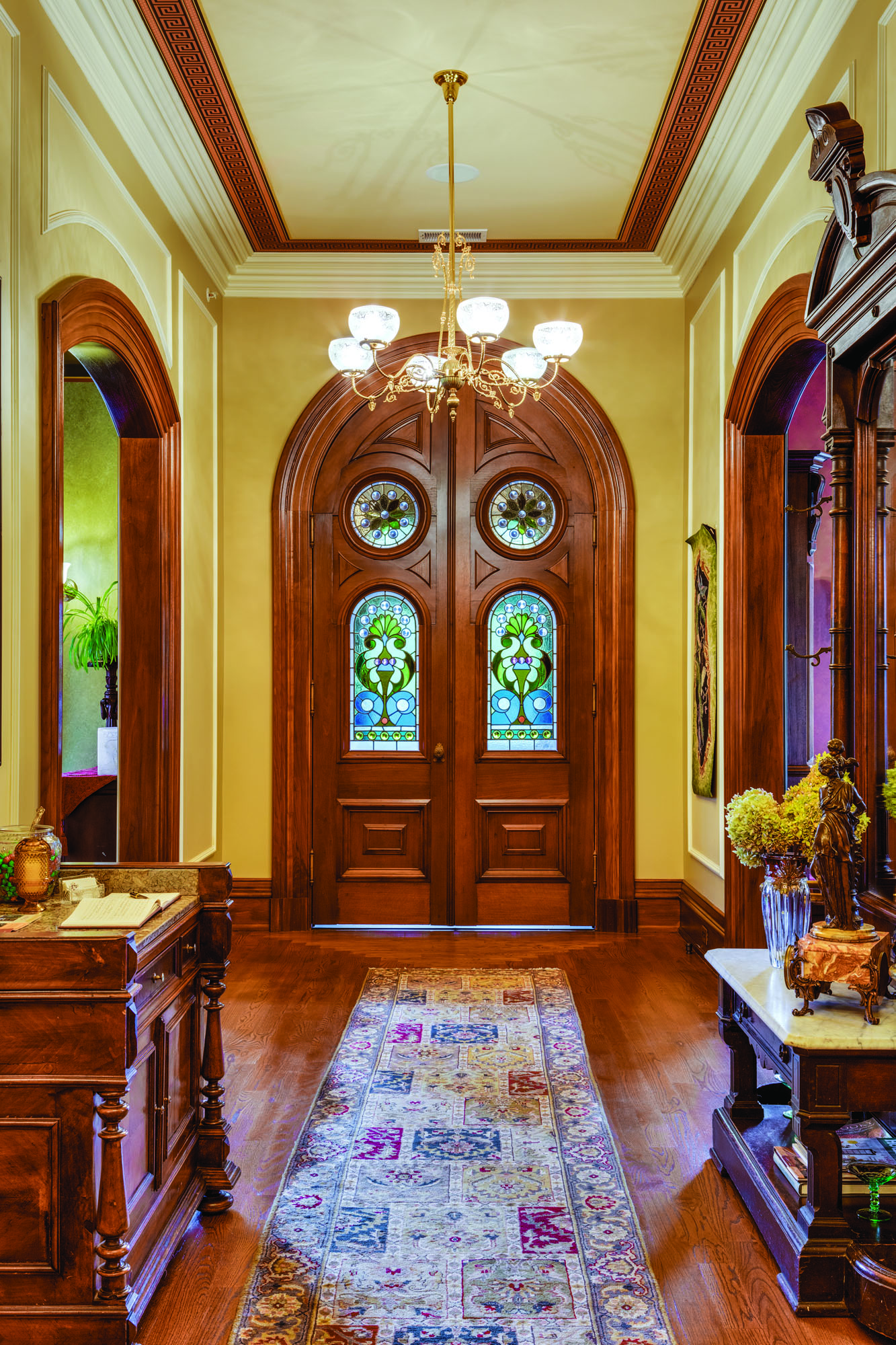 Though severely bowed by the fire, stained-glass panels in the arched, double-leaf front doors were the ones to survive the fire intact. Encaustic tiles in the vestibule (p. 30) were blackened by soot; muriatic acid restored their color.