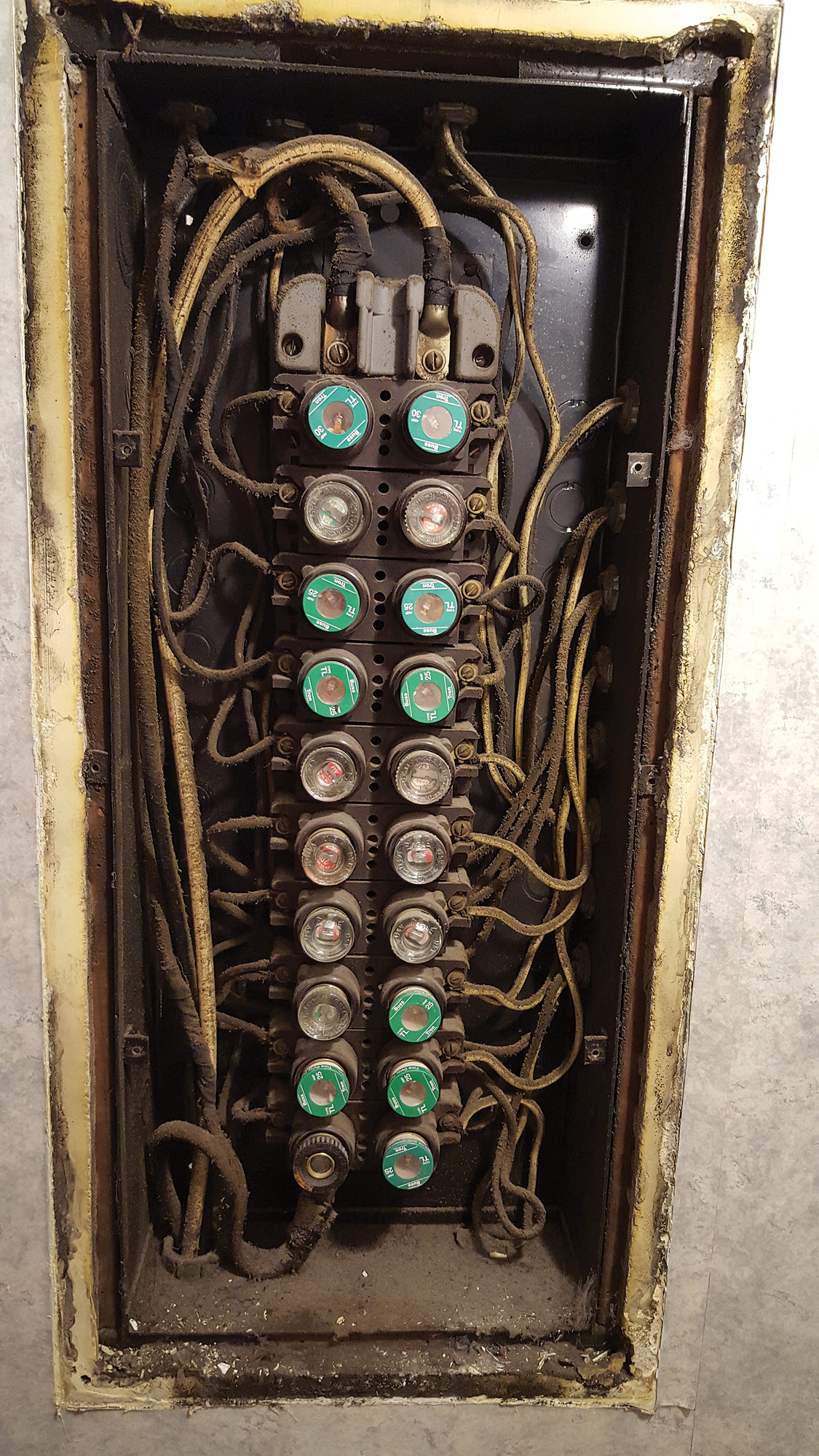 This old fuse box is loaded with obsolete wiring and it lacks adequate  insulation.
