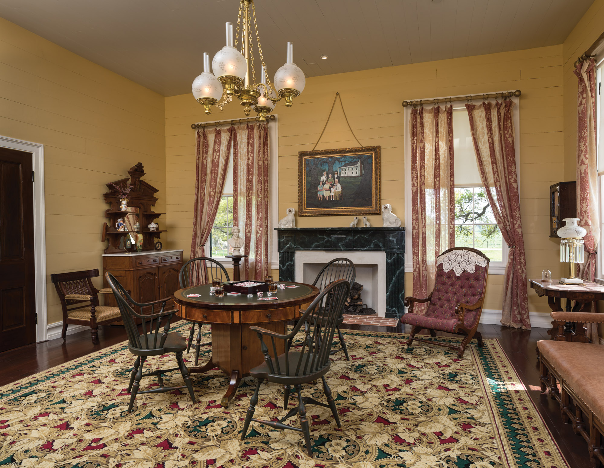 The Gentlemen's Parlor is furnished as a game room. A commissioned painting by contemporary artist George Rodrigue features four generations of Hill ancestors. The chandelier by Jefferson Art Lighting Co. reproduces an 1850s  brass solar fixture.