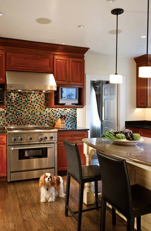 In the kitchen, Bruce kept the existing cabinets intact, but added a mosaic-tile backsplash for a pop of color behind the stove, and a limestone-topped peninsula that provides the family with additional storage and dining space.