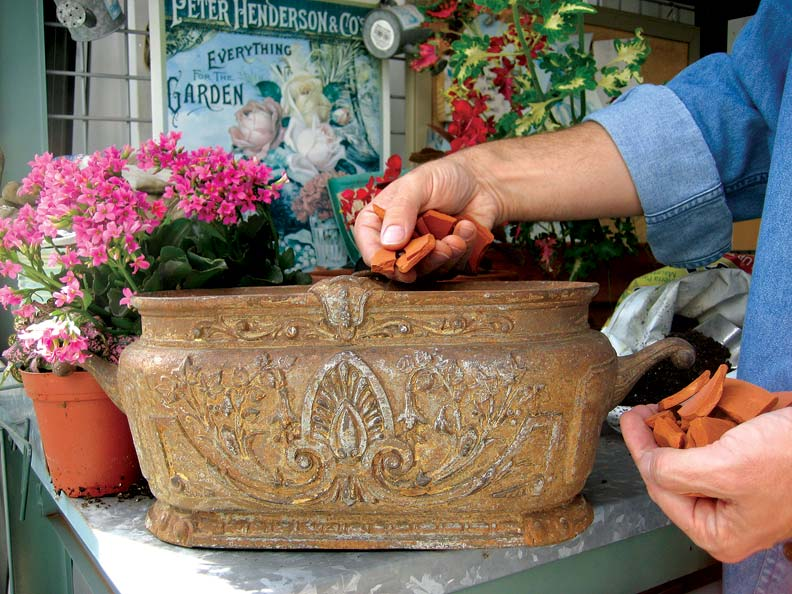 Spreading clay shards on the bottom of an antique urn helps facilitate drainage.