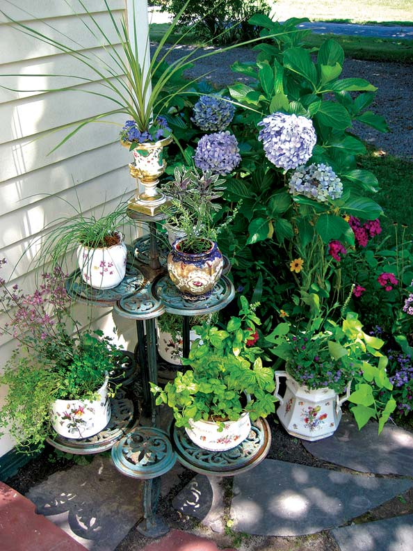 An antique plant stand serves as an outdoor pantry, the vintage containers filled with different herbs.