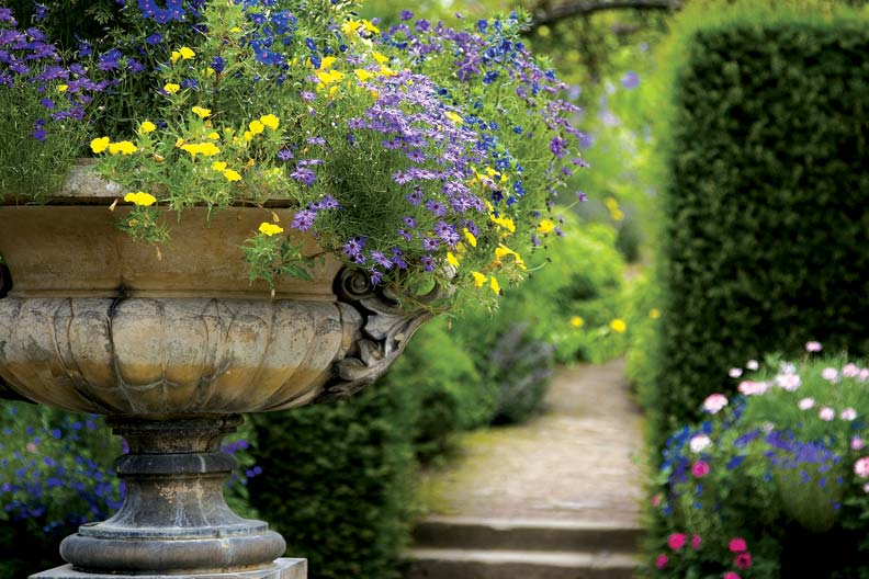 A wide urn serves as an antique sentry for a formal garden entrance.