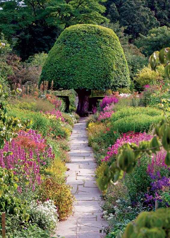 A sculpted tree at the end of a walkway is a stunning addition to the garden.