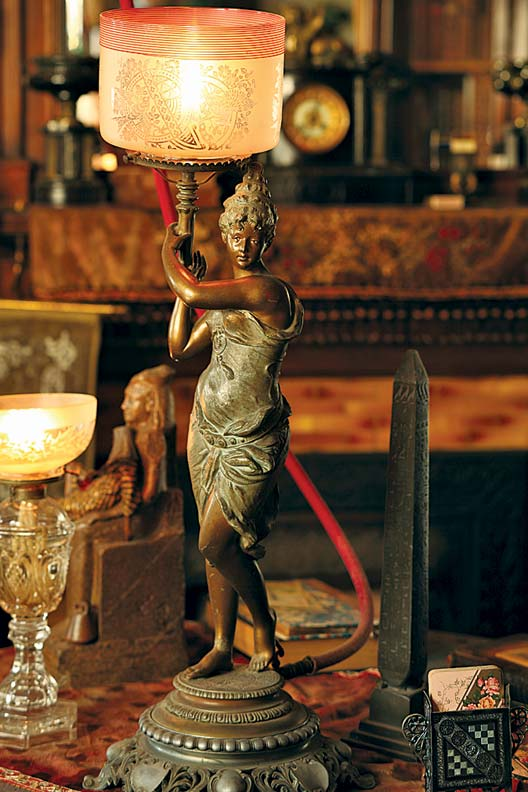 "A lovely Grecian maiden ""portable"" table lamp has a rubber hose that funnels the gas from a chandelier overhead."