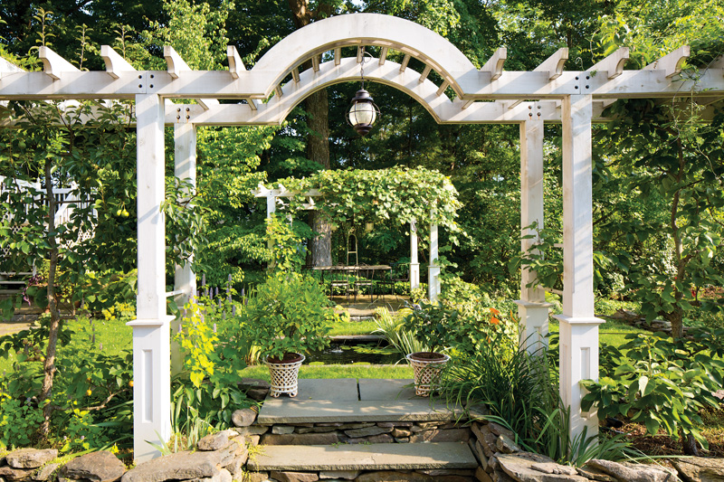 In the backyard, beyond the frog pond, one pergola mirrors another. (Photo credit: Gross & Daley)