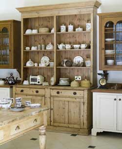 An antique pine dresser is the focal point on this wall, with its collection of old pots, teapots, and plates, all in regular use. The cupboards and glazed-door cabinets on either side were custom-made for glasses an tableware.