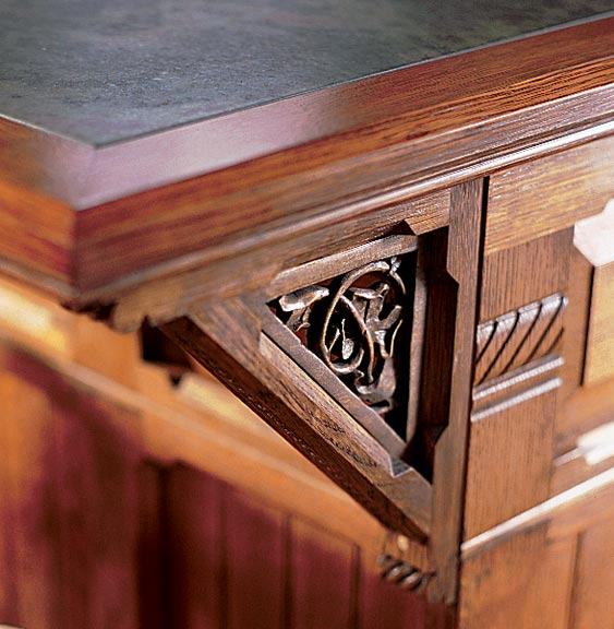 A bracket with a carved leaf and vine motif supports an island countertop.