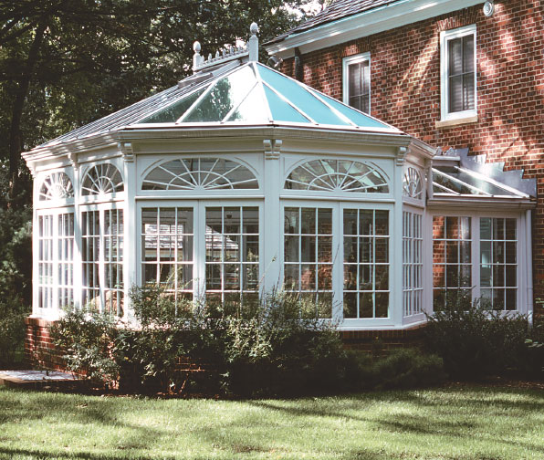 Tanglewood Conservatories of Denton, Maryland, custom-built this ornate glasshouse onto a renovated carriage house.