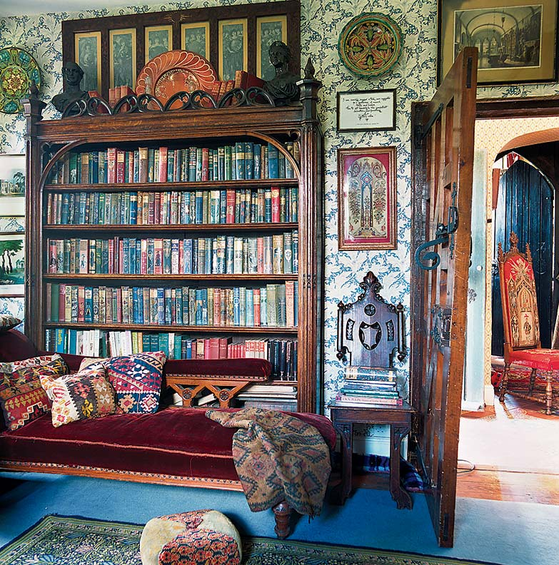 The study's Gothic theme is softened by the floral William Morris wallpaper. Children's books crowd a Victorian Gothic oak bookcase.