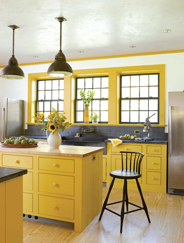 Mellow shades of mustard on the cabinets make the kitchen cheerful. The soapstone sink and counters are reminiscent of the past.