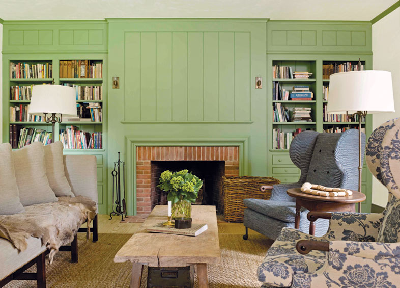Painted paneled walls with bookcases surround a brick fireplace complemented by early American-style chairs.