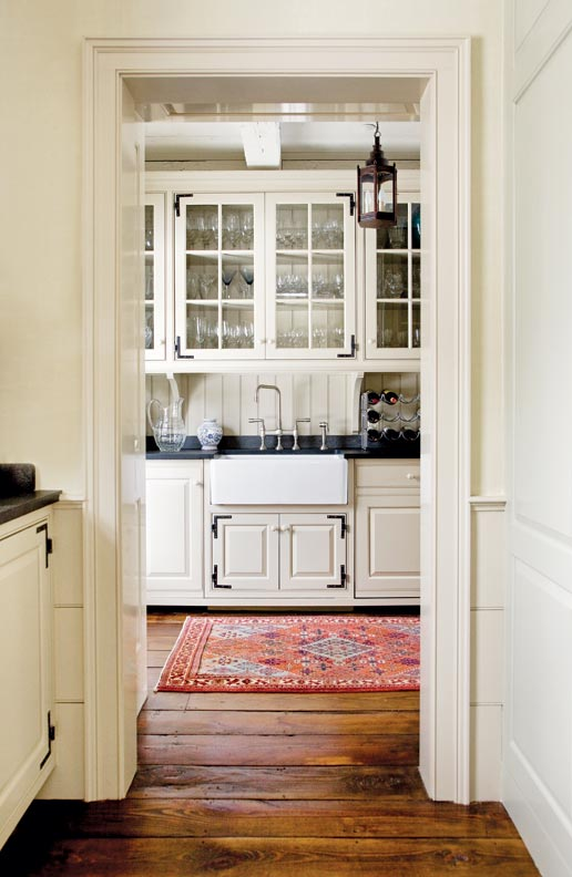 Architect Gil Schafer incorporated a large farmhouse sink, glass cabinets, L-hinges, and a historically inspired lantern in the pantry in this New York new old house.