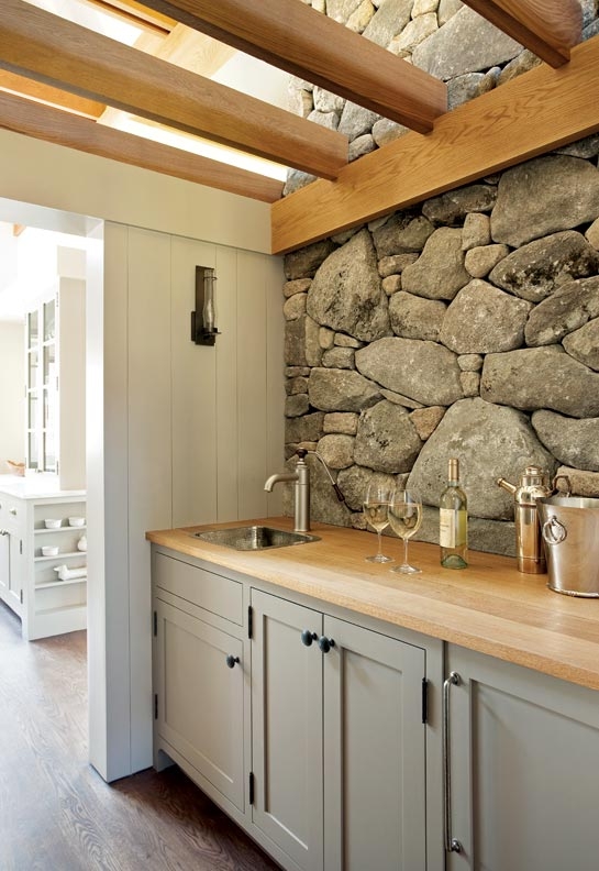 Hutker Architects designed this traditional farmhouse pantry on Martha's Vineyard using natural materials such as stone and wood in conjunction with Shaker-style cabinet profile to enhance the traditional feel.