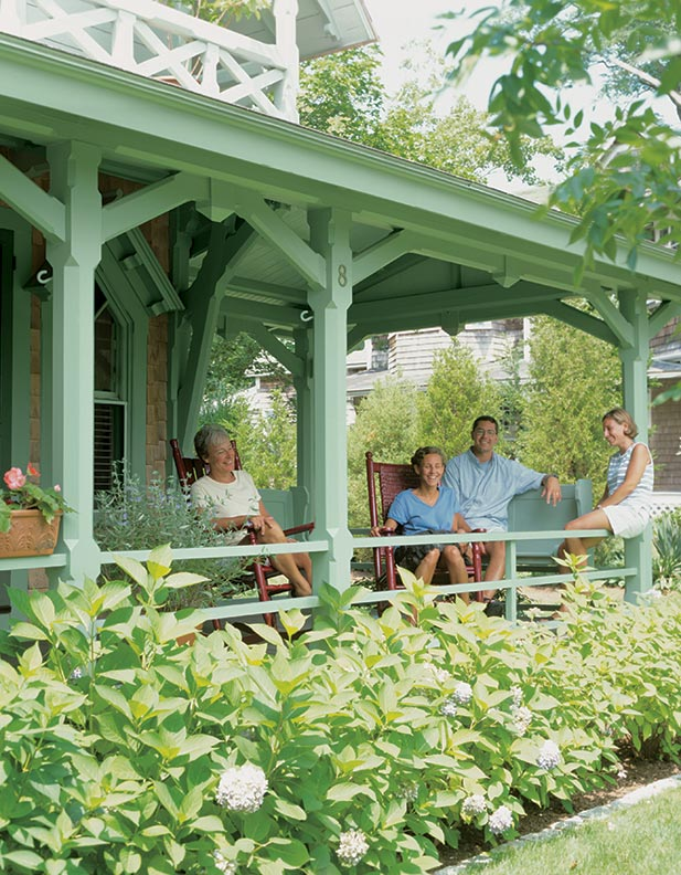 Homeowner Sharon Robinson, daughter Bre, son-in-law Janszen, and daughter Erin relax on the front porch of the Green cottage.