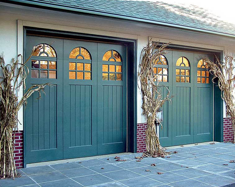 If your goal is to show off your garage door rather than camouflage it, paint it an accent color—here, teal garage doors match other elements on the house, including the entry door and garden gate. (Photo: Designer Doors)