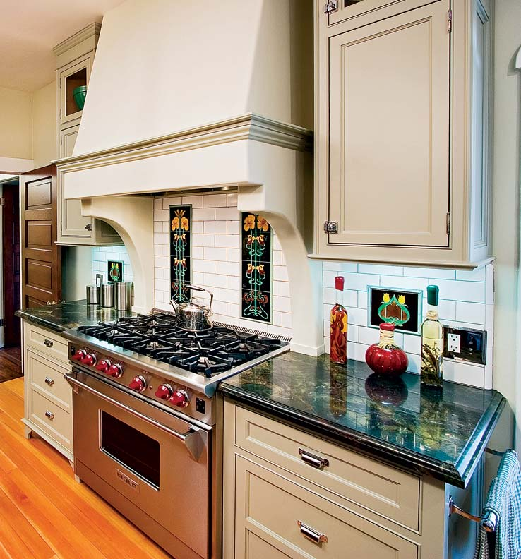 in a field of inexpensive white subway tile, Art Nouveau-style decorative tiles bring a dash of color to the kitchen's otherwise neutral palette.