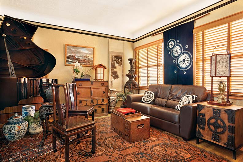 In the living room, a late Edo-period ship's chest (funadansu) acts as end table, and a Meiji-era hibachi doubles as coffee table. A modern shop-entry curtain (noren) hangs between windows. Pillows are faced with antique Japanese ikat (kasuri) fabric.