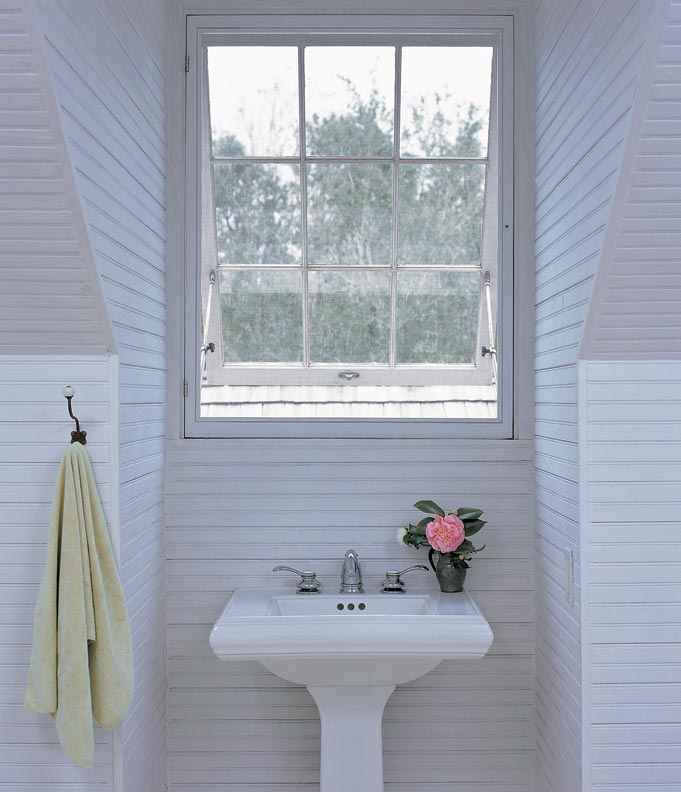 In the master bathroom, a pedestal sink fills a dormer on the back side of the house.