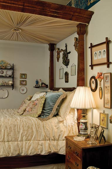 In the master bedroom, an American Empire four-poster bed is surrounded by cherished mementos.