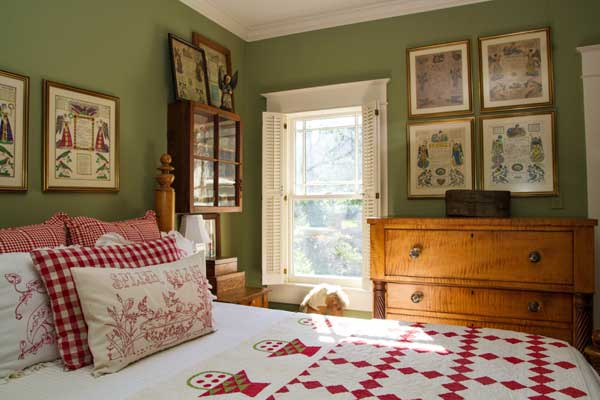 In the master bedroom, white Marseille spreads with red and white accent quilts, coverlets, and pillows are accompanied by samplers as art