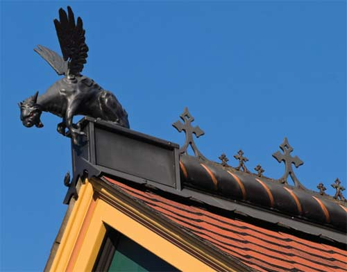 A custom-cast griffin finishes iron roof cresting made from a salvaged cemetery fence.