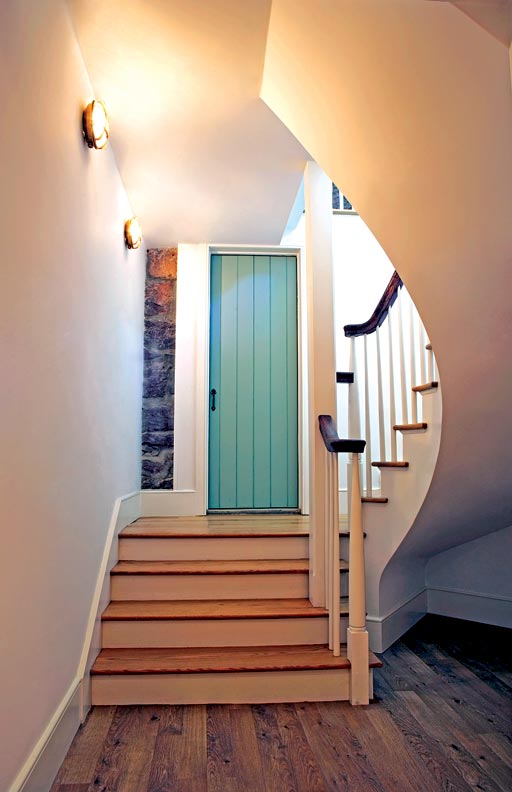 It was important to Maria that the narrow strip of stone next to the green door—part of the home's original foundation—remain exposed to highlight the connection between the old building and new.