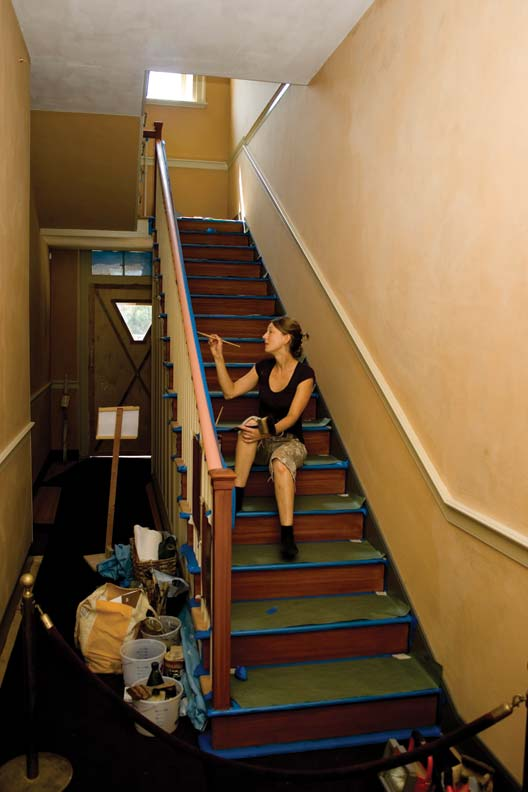 A wood-grain finish is painstakingly applied to the restored staircase.