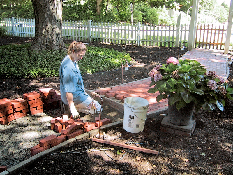 Ideally, this is a two-person job: one levels and lays the bricks, the other cuts bricks to fit small voids in the pattern. (Photo: Bill Ticineto & Jill Chase)